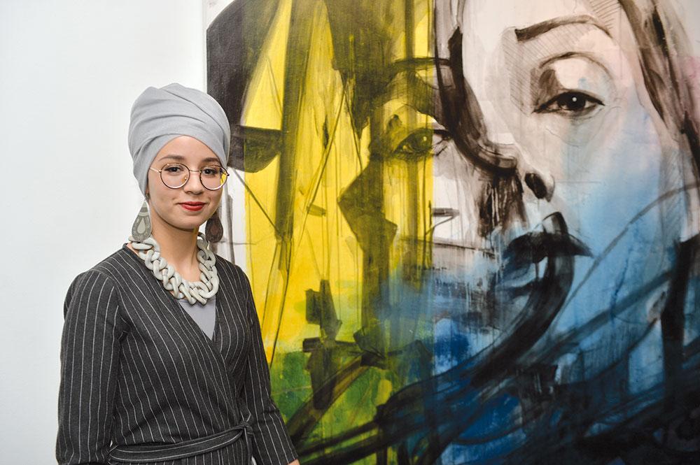 L'artiste peintre Hajar El Moustaassim devant une de ses toiles