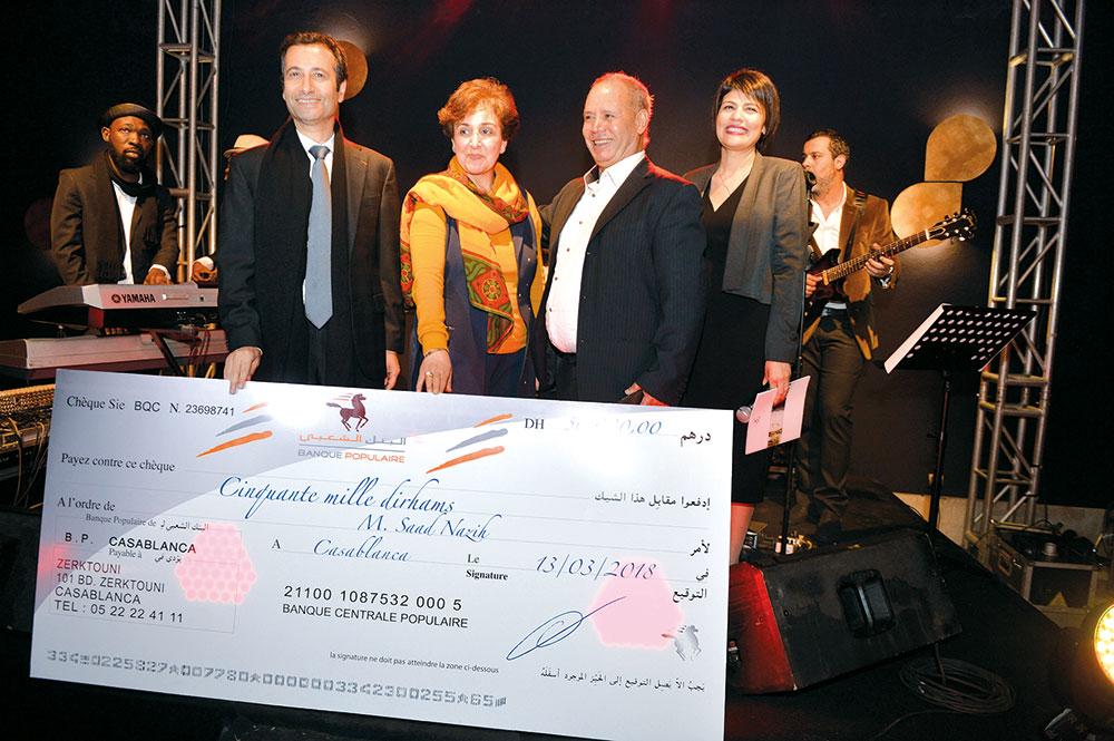 Mohamed Benchaaboun remettant le premier « Prix Banque Populaire pour les jeunes artistes » aux parents de l'artiste Saad Nazih
